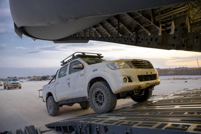 In this Oct. 25, 2019, photo, released by the U.S. Army Reserve, pickup trucks begin loading onto a cargo plane as part of the deliberate withdrawal of forces from northern Syria at the Kobani Landing Zone (KLZ), Syria. Pivoting from the dramatic killing of the Islamic State group's leader, the Pentagon is increasing U.S. efforts to protect Syria's oil fields from the extremist group as well as from Syria itself and the country's Russian allies. It's a new high-stakes mission even as American troops are withdrawn from other parts of the country.(U.S. Army Reserve photo by Staff Sgt. Joshua Hammock via AP)
