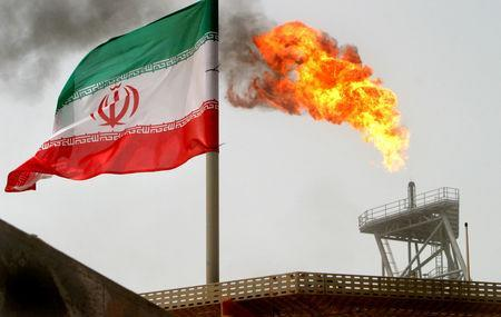 A gas flare on an oil production platform in the Soroush oil fields is seen alongside an Iranian flag in the Persian Gulf, Iran, July 25, 2005. REUTERS/Raheb Homavandi/Files