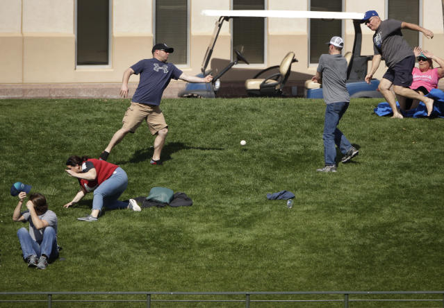 Fans chase a grand slam ball hit by Colorado Rockies' Mark Reynolds during the third inning of a spring training baseball game against the Kansas City Royals, Monday, Feb. 25, 2019, in Surprise, Ariz. (AP Photo/Charlie Riedel)