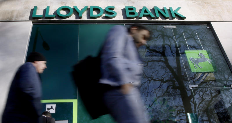 People walk past a branch of Lloyds Bank in London, Thursday, Jan. 28, 2016. Britain's Chancellor George Osborne has announced that the sale of the government's stake in Lloyds Banking Group will be delayed. (AP Photo/Kirsty Wigglesworth)