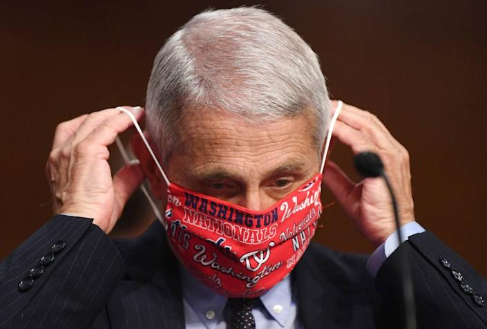 Dr. Anthony Fauci, director of the National Institute for Allergy and Infectious Diseases, lowers his face mask as he prepares to testify before a Senate Health, Education, Labor and Pensions Committee hearing on Capitol Hill in Washington, Tuesday, June 30, 2020.