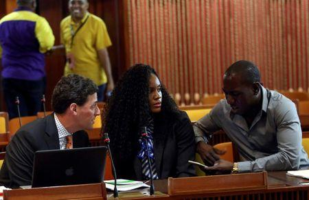 Kaliese Spencer, the reigning Commonwealth Games 400 meters hurdles champion, sits between her attorney Paul Greene and her manager Marvin Anderson, as she attends a meeting with a panel overseeing her anti-doping case in Kingston