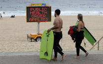 A sign warns people at a beach in Sydney, Australia, Saturday, Dec. 19, 2020. Sydney's northern beaches will enter a lockdown similar to the one imposed during the start of the COVID-19 pandemic in March as a cluster of cases in the area increased to more than 40. (AP Photo/Mark Baker)