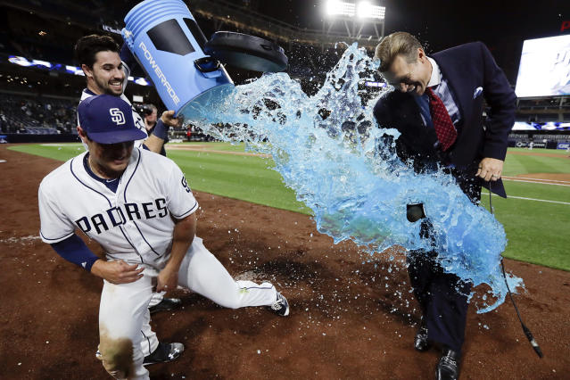 <p>San Diego Padres' Hunter Renfroe, left, dodges energy drink dumped by teammate Austin Hedges after hitting a walk-off home run during the tenth inning of a baseball game against the Milwaukee Brewers, May 15, 2017, in San Diego. A reporter ready to interview Renfroe stands by at right. The Padres won, 6-5. (Photo: Gregory Bull/AP) </p>