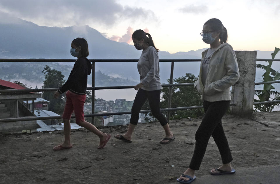 Naga girls wearing face masks as a precautionary measure against the coronavirus walk at dusk in Kohima, capital of the northeastern Indian state of Nagaland, Thursday, Oct. 29, 2020. India's confirmed coronavirus caseload surpassed 8 million on Thursday with daily infections dipping to the lowest level this week, as concerns grew over a major Hindu festival season and winter setting in. (AP Photo/Yirmiyan Arthur)