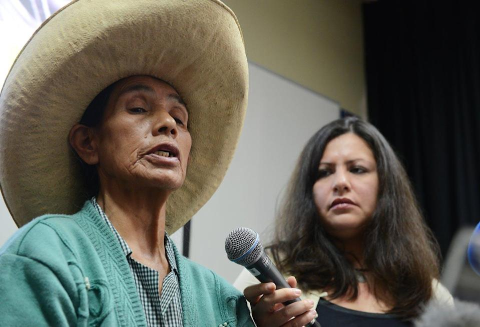 Older woman in green shirt and straw hat speaks into a microphone held by a younger woman