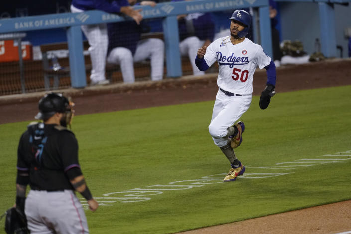 Los Angeles Dodgers' Mookie Betts (50) runs home to score off of a single hit by Max Muncy during the fifth inning of a baseball game against the Miami Marlins Saturday, May 15, 2021, in Los Angeles. (AP Photo/Ashley Landis)