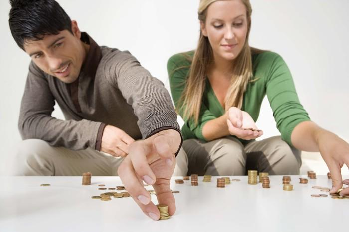 A millennial couple counting coins on a table.
