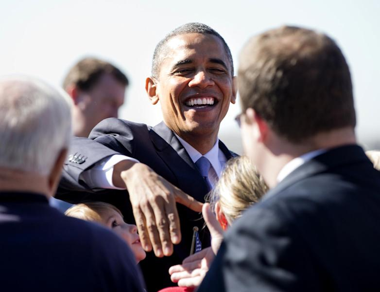 President Barack Obama greets people on the tarmac as he arrives at Manchester Boston Regional Airport, Thursday, Oct. 18, 2012, in Manchester, N.H., for a campaign stop. (AP Photo/Carolyn Kaster)