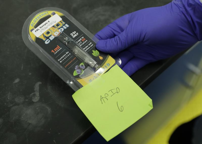 A researcher holds a Yolo! brand CBD vape oil cartridge and its packaging at Flora Research Laboratories in Grants Pass, Ore., on July 17, 2019.  Authorities blamed Yolo for sending people to emergency rooms in Utah, saying it contained a dangerous synthetic marijuana. The cartridge pictured here was provided to The Associated Press by a South Carolina man who says he nearly died after puffing it. Testing commissioned by AP shows it contained the same synthetic marijuana that caused the illnesses in Utah.  (AP Photo/Ted Warren)