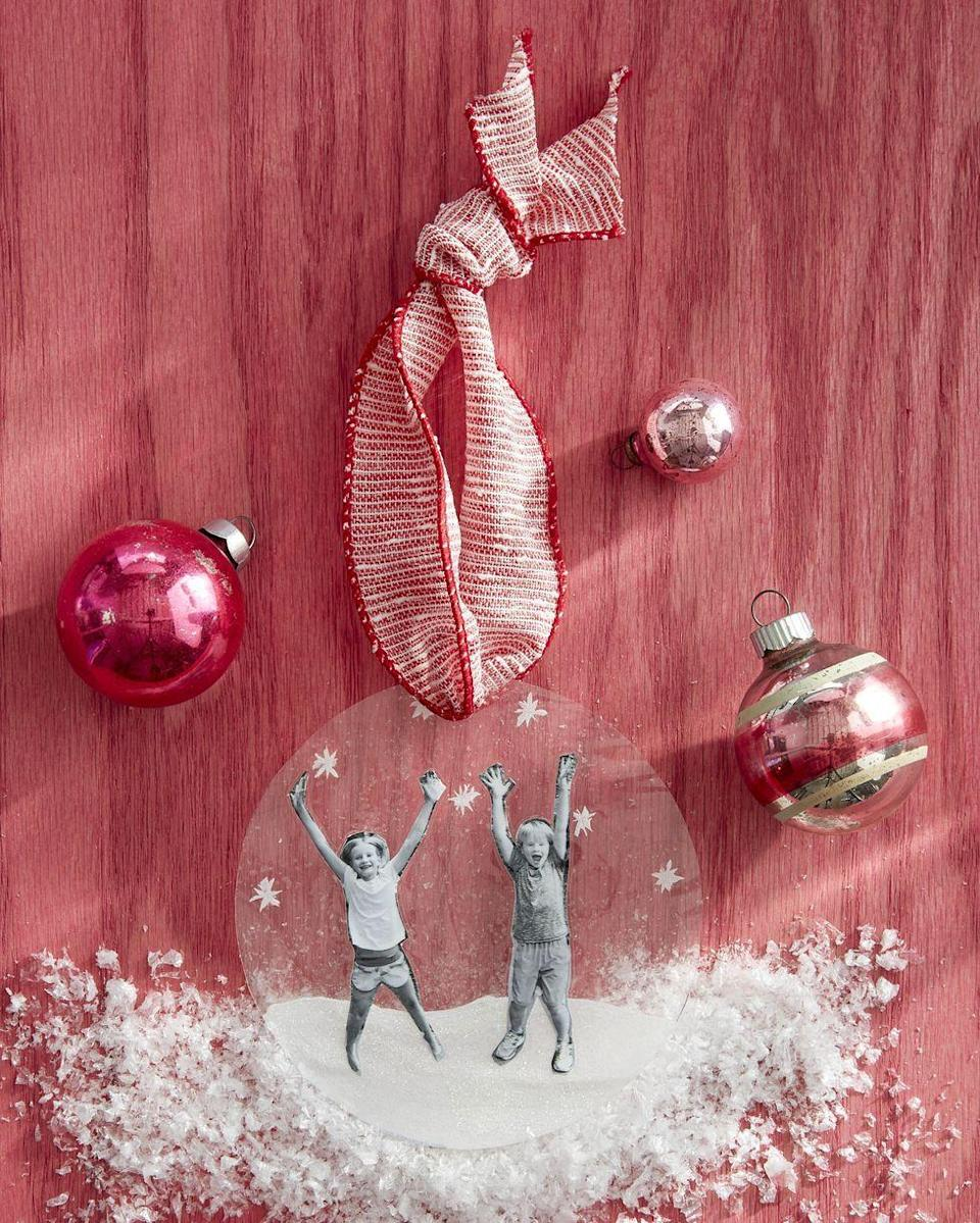 """<p>A perfect gift for the grands, this ornament places the kids inside a wintry wonderland of sparkling snow.</p><p><strong>To make</strong><strong>:</strong> Cut out photographs. Cut out snow and snowflakes from glittery craft paper. Set imagery on one sheet of laminating paper. Top with a second sheet and run through the laminating machine. Cut out ornament to desire shape. Punch a hole in the top; thread a ribbon through the hole to hang.</p><p><a class=""""link rapid-noclick-resp"""" href=""""https://www.amazon.com/s?k=white+glittery+craft+paper&ref=nb_sb_noss_2&tag=syn-yahoo-20&ascsubtag=%5Bartid%7C10050.g.645%5Bsrc%7Cyahoo-us"""" rel=""""nofollow noopener"""" target=""""_blank"""" data-ylk=""""slk:SHOP GLITTER CRAFT PAPER"""">SHOP GLITTER CRAFT PAPER</a></p>"""