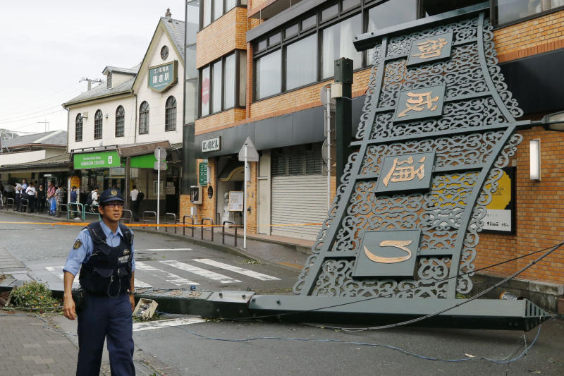A police officer walks past a fallen signboard hit by typhoon at a shopping district in Kamakura, near Tokyo Monday, Sept. 9, 2019. (Kyodo News via AP)