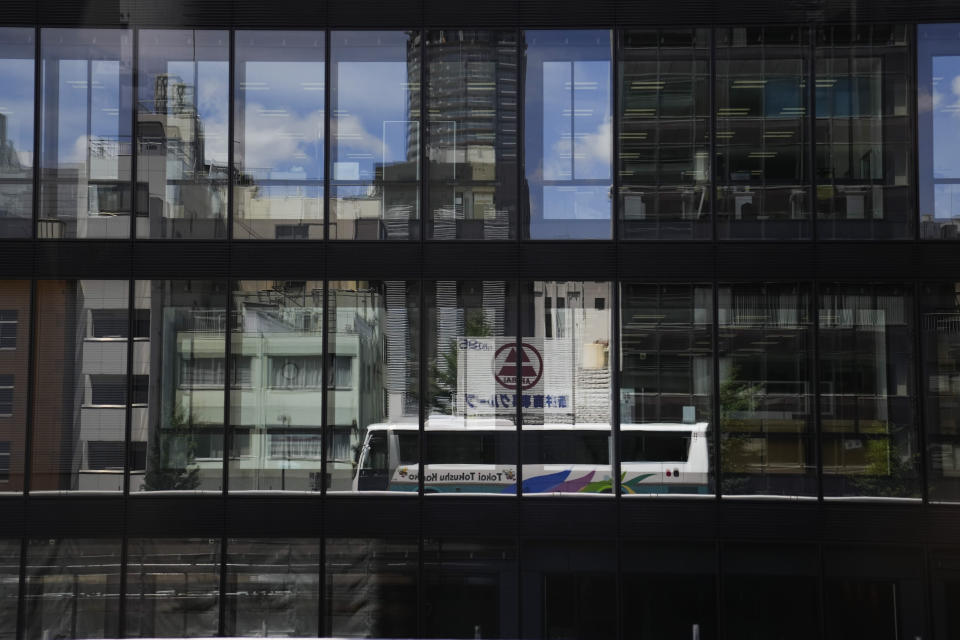 A bus carrying members of the media is reflected on glass windows of a building ahead of the 2020 Summer Olympics, Friday, July 16, 2021, in Tokyo. The pandemic-delayed games open on July 23 without spectators at most venues. (AP Photo/Jae C. Hong)