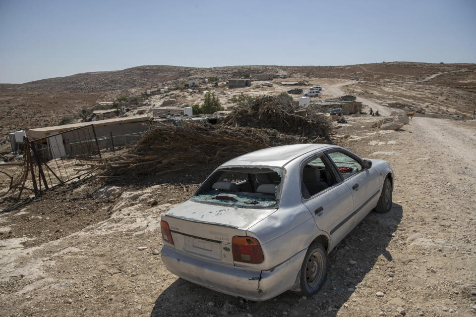 A vehicle damaged following a settlers' attack from nearby settlement outposts on the Palestinian Bedouin community, in the West Bank village of al-Mufagara, near Hebron, Thursday, Sept. 30, 2021. An Israeli settler attack last week damaged much of the village's fragile infrastructure. (AP Photo/Nasser Nasser)