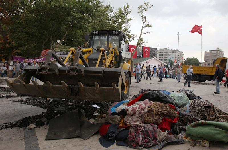 A bulldozer cleans the entrance of Gezi Park from debris in Istanbul, Saturday, June 15, 2013. Protesters will press on with their sit-in at an Istanbul park, an activist said Saturday, defying government appeals and a warning from Prime Minister Recep Tayyip Erdogan for the two-week standoff that has fanned nationwide demonstrations to end. (AP Photo/Thanassis Stavrakis)