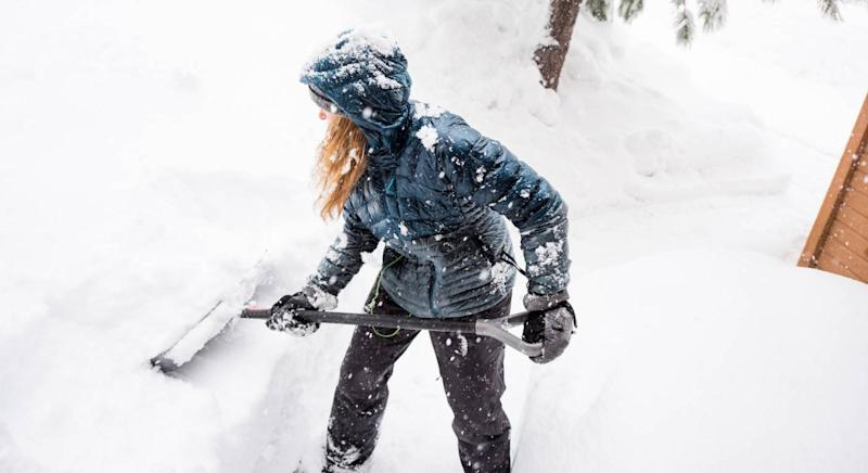 Woman shovels snow from her driveway [Photo: Getty]