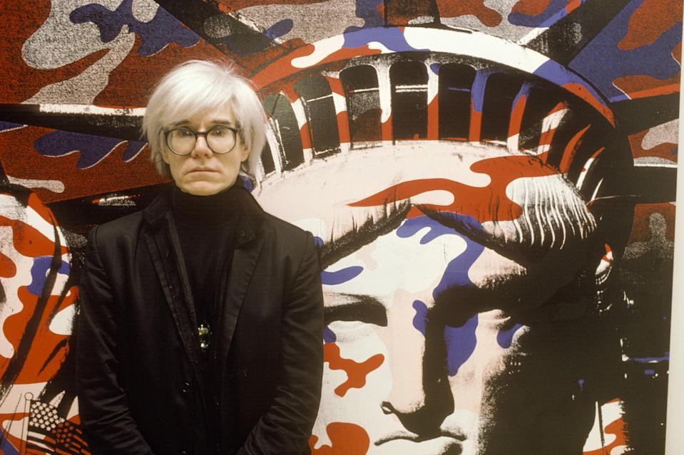 """Andy Warhol in front of one of his """"Statue of Liberty (Fabis)"""" series paintings in Paris. <a href=""""https://www.thebroad.org/art/andy-warhol/statue-liberty-fabis"""" rel=""""nofollow noopener"""" target=""""_blank"""" data-ylk=""""slk:This painting"""" class=""""link rapid-noclick-resp"""">This painting</a> is now in Los Angeles, in the <a href=""""https://www.cntraveler.com/activities/los-angeles/los-angeles/the-broad-museum?mbid=synd_yahoo_rss"""" rel=""""nofollow noopener"""" target=""""_blank"""" data-ylk=""""slk:Broad Museum's"""" class=""""link rapid-noclick-resp"""">Broad Museum's</a> collection, while a yellow colorway is a part of the <a href=""""https://youtu.be/ZjgAd6Z-dd0"""" rel=""""nofollow noopener"""" target=""""_blank"""" data-ylk=""""slk:Tate Modern's Warhol exhibit"""" class=""""link rapid-noclick-resp"""">Tate Modern's Warhol exhibit</a> in London."""