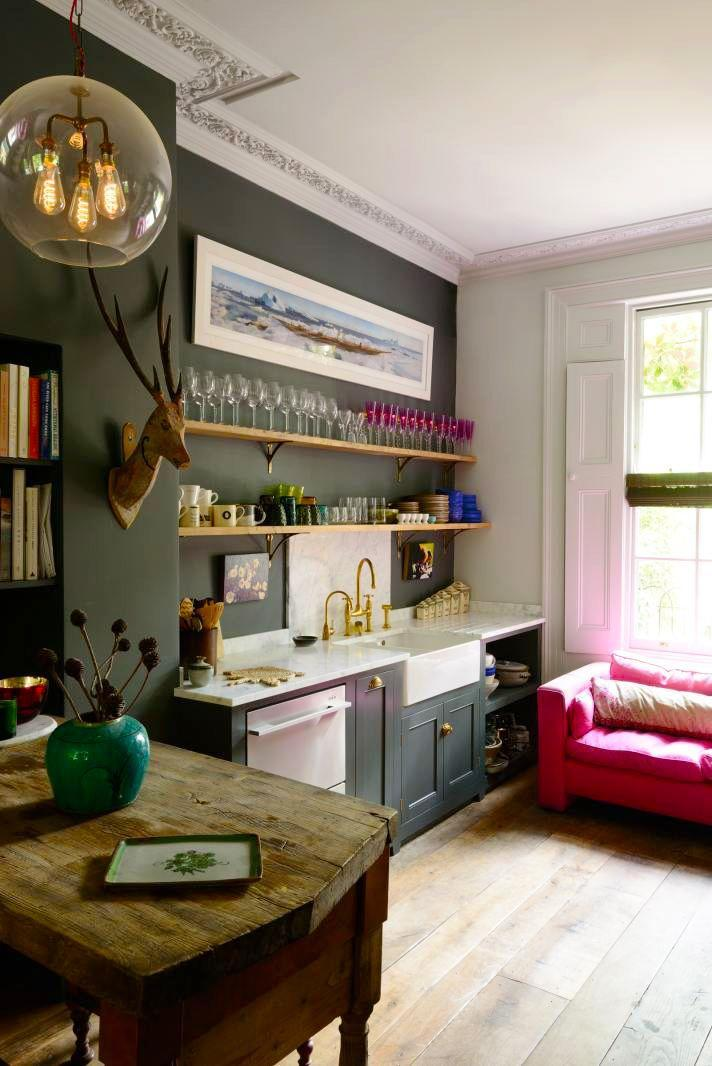 <p>Why hide your favorite glassware behind closed cabinets when they can be displayed out in the open, doubling as decor? The magenta wine glasses in this deVOL Kitchens townhouse accentuate the statement sofa. </p>