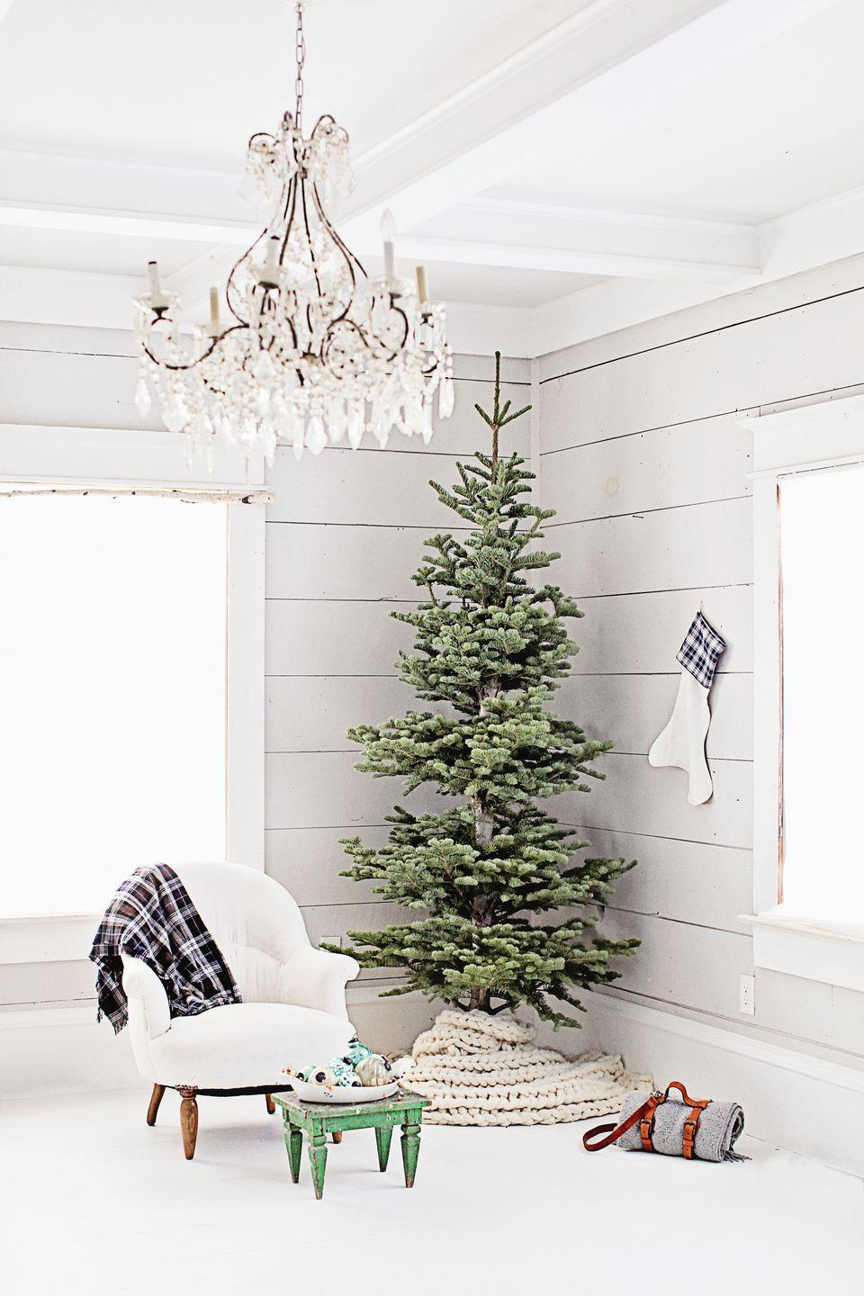 "<p>A skinny, unadorned tree in a creamy <a href=""https://www.elledecor.com/design-decorate/color/g304/white-walls/"" rel=""nofollow noopener"" target=""_blank"" data-ylk=""slk:white room"" class=""link rapid-noclick-resp"">white room</a> is perhaps a minimalist's dream. This design by <a href=""https://www.instagram.com/p/-ZS3-TvFpr/"" rel=""nofollow noopener"" target=""_blank"" data-ylk=""slk:Dreamy Whites"" class=""link rapid-noclick-resp"">Dreamy Whites</a> improvises a tree skirt from a blanket and adds a white-and-plaid stocking nearby for good measure. </p>"