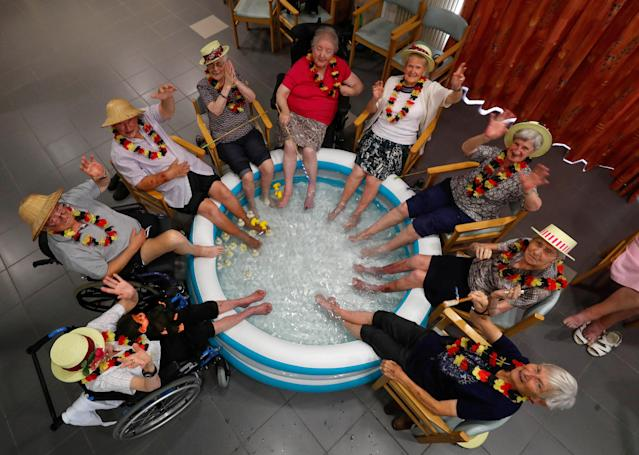 <p>Residents at the Ter Biest house for elderly persons refresh their feet in a pool on a hot summer day, in Grimbergen, Belgium, Aug. 3, 2018. (Photo: Yves Herman/Reuters) </p>