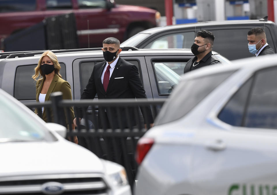 Nauman Hussain, second from left, who is charged with 20 counts of second degree manslaughter and criminally negligent homicide in the 2018, limousine crash walks into a converted courtroom to accommodate more people at the Schoharie High School gymnasium Thursday, Sept. 2, 2021, in Schoharie, N.Y. (AP Photo/Hans Pennink)