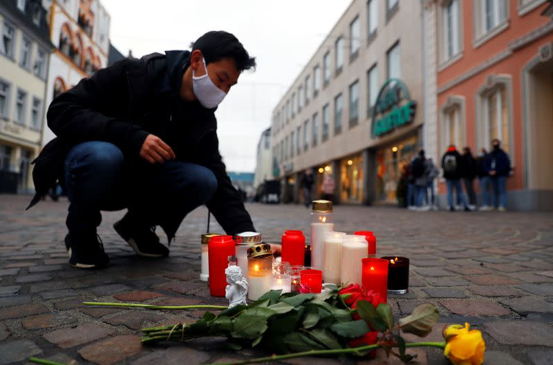 A person pays his respect at the site where a car crashed into pedestrians in Trier