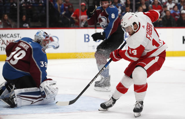 Colorado Avalanche goaltender Pavel Francouz, left, stops a shot off the stick of Detroit Red Wings center Robby Fabbri, right, as Avalanche defenseman Cale Makar (8) trails the play in the second period of an NHL hockey game Monday, Jan. 20, 2020, in Denver. (AP Photo/David Zalubowski)