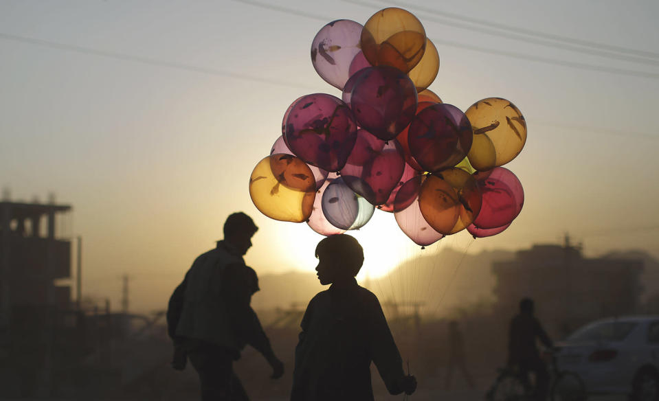 <p>Afghan boy Mahfouz Bahbah, 12, stands on a roadside hoping to sell his balloons during sunset in Kabul, Afghanistan, Oct. 18, 2011. (Photo: Muhammed Muheisen/AP) </p>