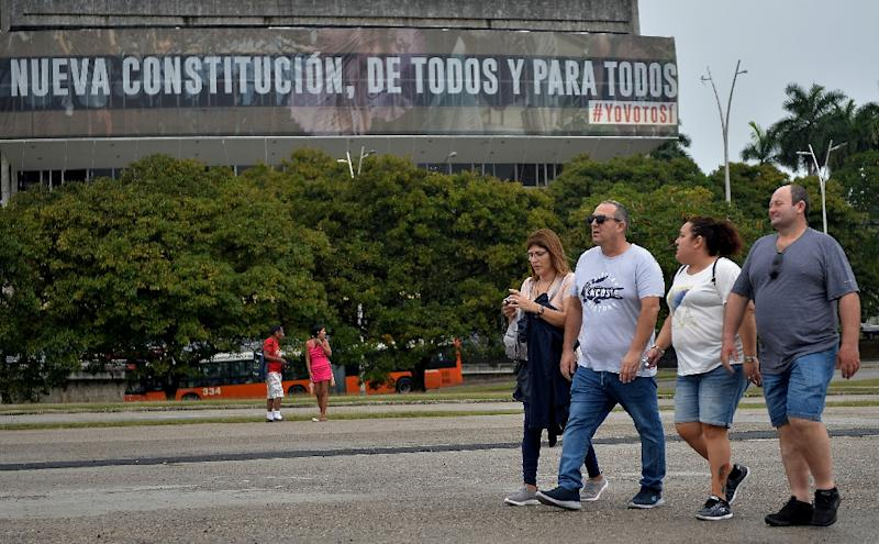 A group of tourists walks in February 2019 past a billboard with revolutionary slogans in Havana, which had become increasingly attractive to US visitors amid a thaw led by president Barack Obama (AFP Photo/YAMIL LAGE)