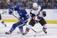 Toronto Maple Leafs center Auston Matthews (34) and Arizona Coyotes right wing Vinnie Hinostroza (13) battle for the puck during first period NHL hockey action in Toronto on Tuesday Feb. 11, 2020. (Nathan Denette/The Canadian Press via AP)