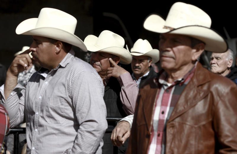 Residents listen to Mexico's President Andres Manuel Lopez Obrador during his visit to the small town of La Mora, Sonora state, Mexico, Sunday Jan. 12, 2020. Lopez Obrador said Sunday there is an agreement to establish a monument will be put up to memorialize nine U.S.-Mexican dual citizens ambushed and slain last year by drug gang assassins along a remote road near New Mexico. (AP Photo/Christian Chavez)