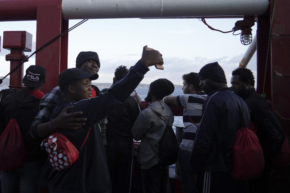 A couple takes a selfie as they wait to disembark from aboard the Ocean Viking ship as it reaches the port of Messina, Italy, Tuesday, Sept. 24, 2019. The humanitarian ship has docked in Italy to disembark 182 men, women and children rescued in the Mediterranean Sea after fleeing Libya. (AP Photo/Renata Brito)