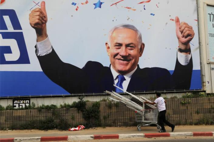 A man walks past a Likud party election campaign banner depicting its leader, Israeli Prime Minister Benjamin Netanyahu, ahead of the March 23 ballot, in Bnei Brak