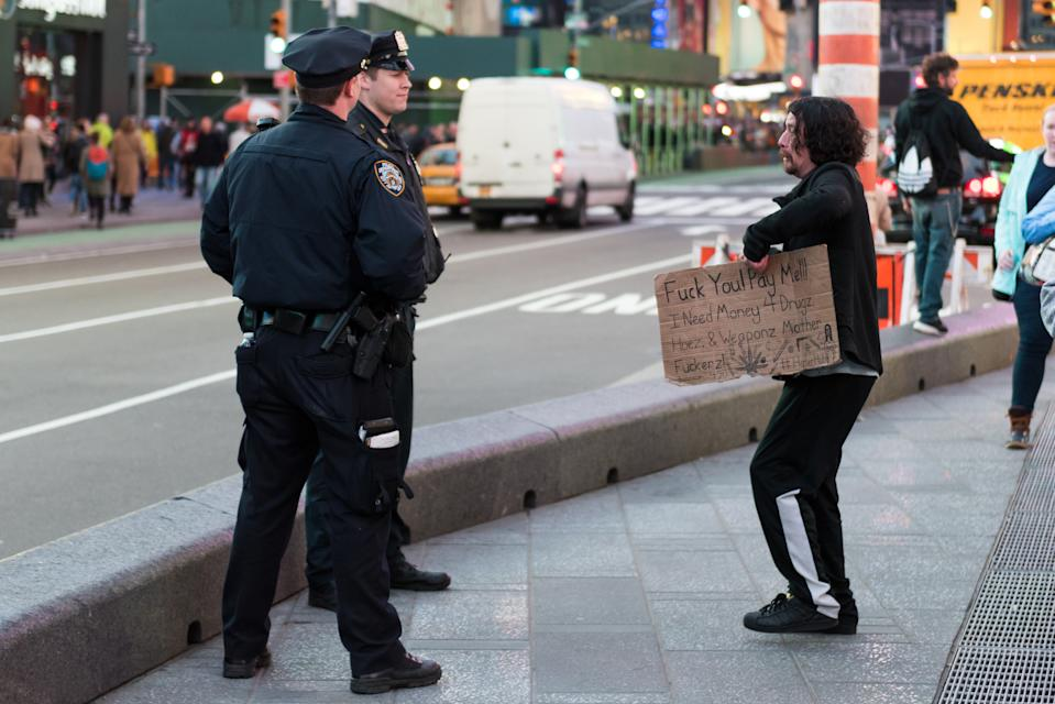 """New York, USA – April 4th, 2017: A man holding a sign that reads """"Fuck You! Pay Me!!! I Need Money 4 Drugz."""" talking with the NYPD late in the day in Times Square."""