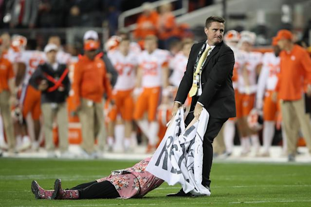 A woman appeared to be staging a protest at Monday's title game and was dragged off the field by police. (Getty)