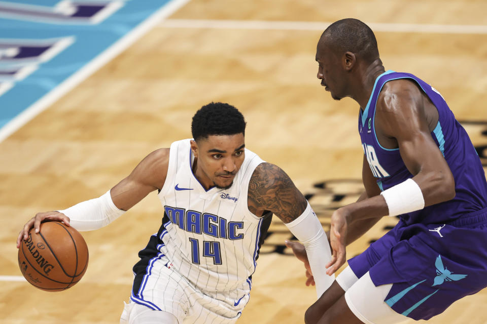 Orlando Magic guard Gary Harris (14) drives on Charlotte Hornets center Bismack Biyombo during the second half of an NBA basketball game in Charlotte, N.C., Friday, May 7, 2021. (AP Photo/Nell Redmond)