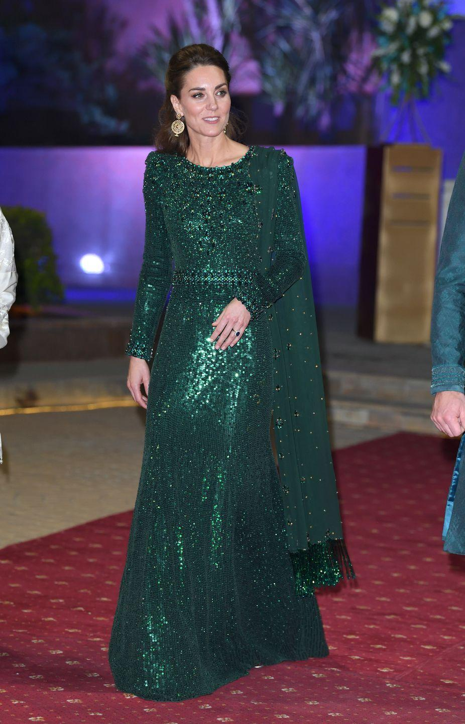<p>During a state visit to Pakistan, Kate Middleton dazzled in an emerald sequin Jenny Packham gown. The Duchess finished the long sleeve gown with a matching chiffon scarf and gold statement earrings. </p>