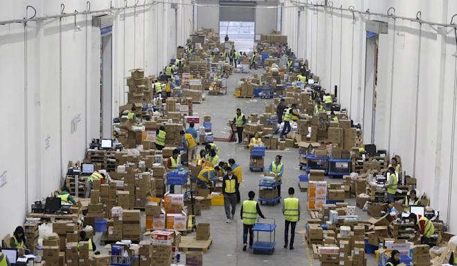 Employees sort boxes and parcels at the logistic centre of an express delivery company in Wuhan, Hubei province on November 12, 2015. Photo: Reuters