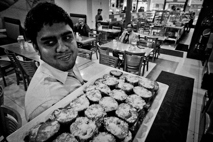<p>Saifur Rahman Shawon carries a tray full of sweets at Premium restaurant on 73rd Street in an area known as Little Bangladesh in Jackson Heights, Queens, N.Y., in December 2015. (Photo: Yunghi Kim/Contact Press Images) </p>