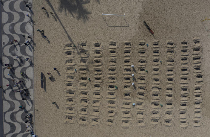 Activists dig the symbolic graves on Copacabana Beach. (AP)