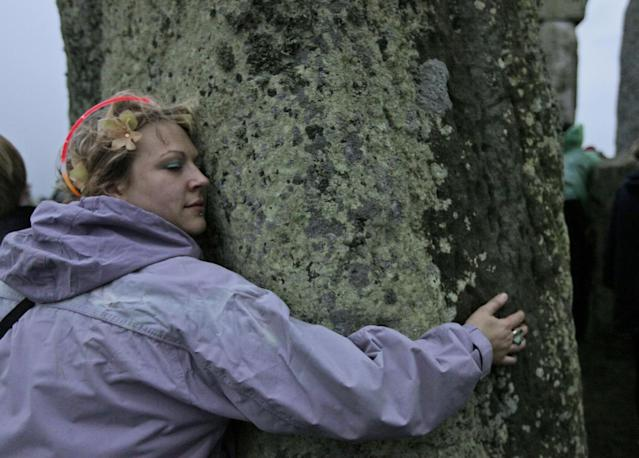 A woman hugs a stone pillar at the Stonehenge monument during the summer solstice at Stonehenge, near Salisbury Thursday, June 21, 2012. Rain-sodden crowds welcomed a spectacularly rainy summer solstice at Stonehenge in true British fashion Thursday: With stoicism and wit. But through the wind and rain, drummers inside the ancient stone circle kept up their thumping rhythm, new age pagans kept up their chaotic dance, and visitors kept up their sense of humor. (AP Photo/Lefteris Pitarakis)