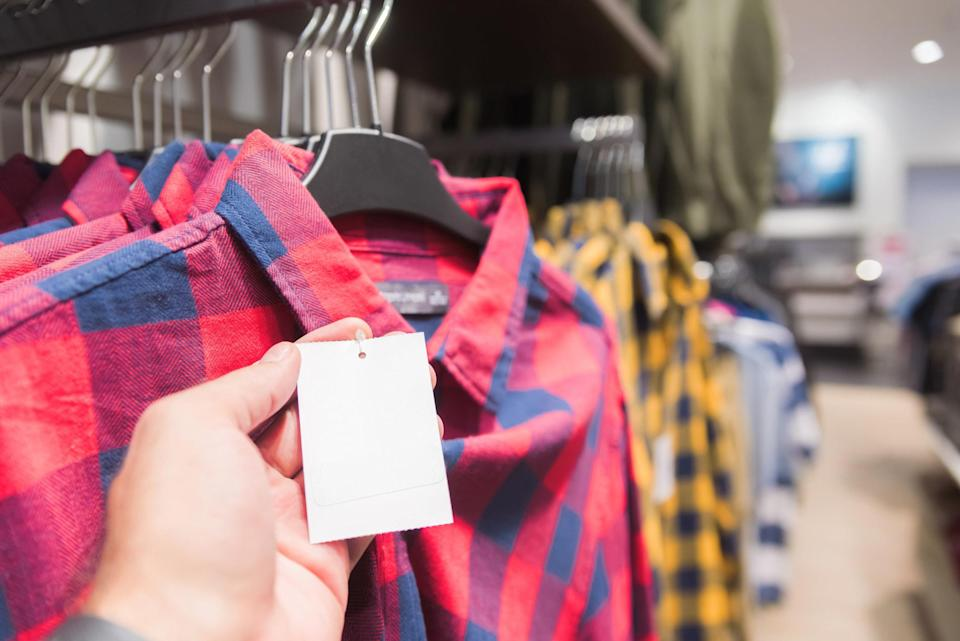 Yellow and red flannel with a blurred background and the buyer's hand checking the price