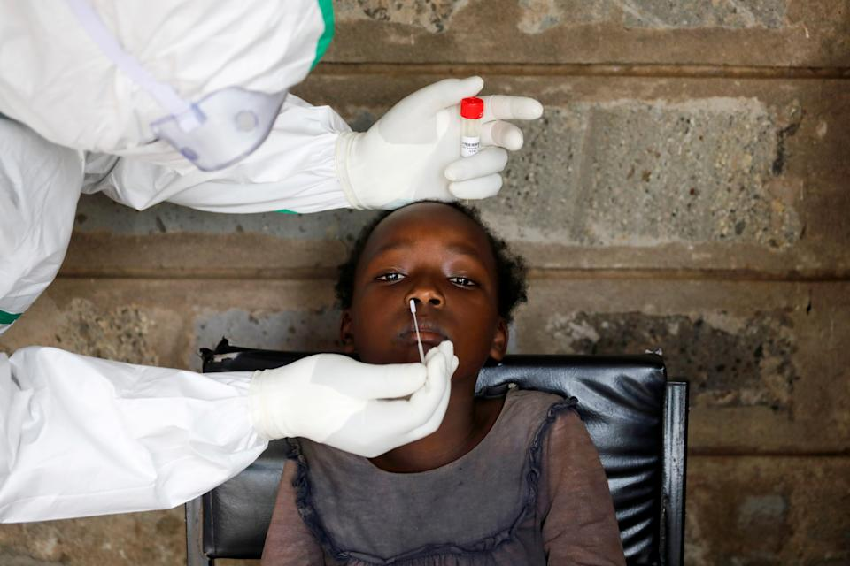 A health worker collects a swab sample from a young girl during free mass testing for the coronavirus disease (COVID-19) in Kibera slums of Nairobi, Kenya, October 17, 2020. REUTERS/Baz Ratner     TPX IMAGES OF THE DAY