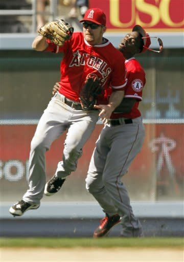 Los Angeles Angels leftfielder Ryan Langerhans, left, has snagged a fly off the Los Angeles Dodgers' Jeff Bailey as centerfielder Travis Witherspoon charges into him inthe eighth inning of a Freeway Series exhibition baseball game at Dodger Stadium in Los Angeles, Wednesday, April 4, 2012. The Angels won 8-3. (AP Photo/Reed Saxon)