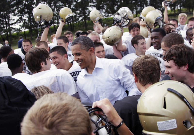 FILE - In this Aug. 17, 2011 file photo, President Barack Obama huddles with the Galesburg High School football team in Galesburg, Ill., during a three-day economic bus tour. The president has developed a lasting tie to this small, economically bruised town with an empty refrigerator plant and a liberal arts college where he likes to roll-out big economy speeches. He is scheduled to give an economic speech at Knox College in Galesburg on Wednesday, July 24, 2013. (AP Photo/Carolyn Kaster, File)