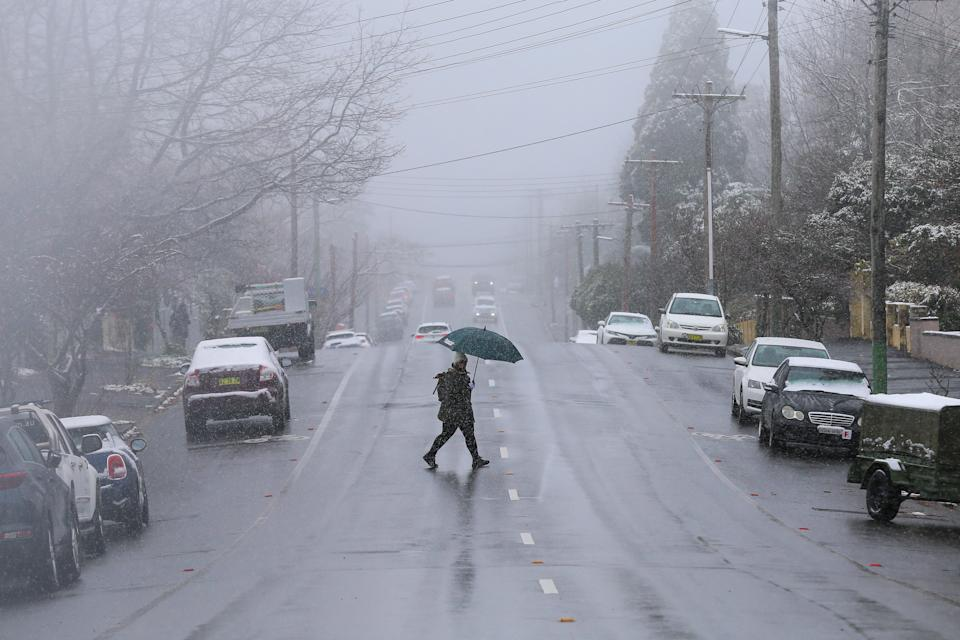 A person crosses the street during snowfall in Katoomba, NSW. Source: AAP