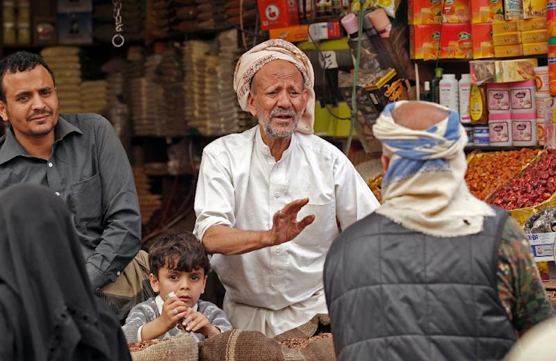 A Yemeni vendor speaks with a costumer in a market in the old city of the capital Sanaa, as the faithful prepare for the Muslim holy fasting month of Ramadan, on May 2, 2019 (AFP Photo/MOHAMMED HUWAIS)
