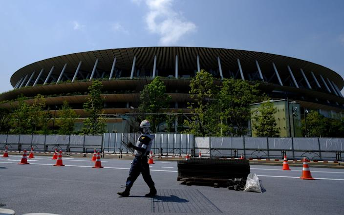 Workers install additional security fence outside Olympic Stadium (National Stadium) for the 2020 Tokyo Olympic Games, that have been postponed to 2021 due to the coronavirus disease - Reuters