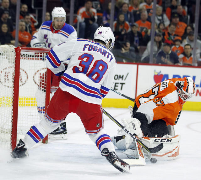 Philadelphia Flyers' Brian Elliott defends the goal as New York Rangers' Steven Fogarty attacks during the first period of an NHL hockey game Saturday, April 7, 2018 in Philadelphia, PA. (AP Photo/Tom Mihalek)