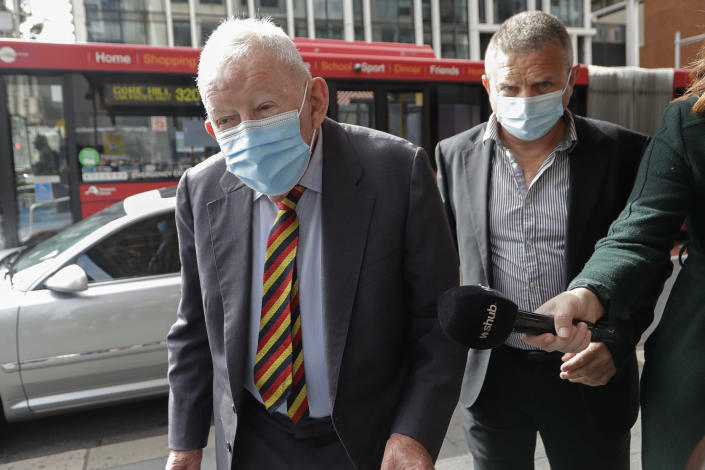 New Zealand businessmen Ron Brierley, left, arrives at the Local Downing Centre Court in Sydney, Thursday, Oct. 14, 2021, to be sentenced for possessing child sex abuse images. Brierley, one of New Zealand's most well-known businessmen, was sentenced to 14 months in prison for possessing child sex abuse images. (AP Photo/Rick Rycroft)